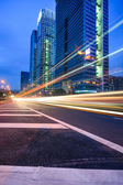 Traffic trails at twilight on the cityscape background — Stock Photo