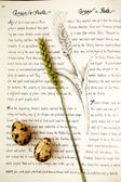 Small eggs and wheat over an old book — Stock Photo