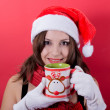 Woman holding tea cup on red background — Stock Photo