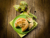 Vegetarian quiche with artichoke on wood background — Stock Photo