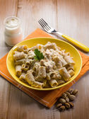Pasta with fish ragout pistachio and cream sauce — Stock Photo