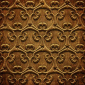 Carved ornament on wooden texture — Stock Photo