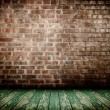 Old interior with brick wall and wooden floor — Stock Photo
