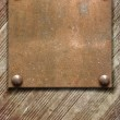 Metal plate on wooden background — Stock Photo
