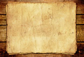 Old paper sheet on wooden background — Stock Photo
