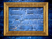 Golden frame on blue urban brick wall — Stock Photo