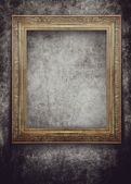 Golden frame on grunge black wall — Photo