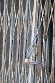 Vorhängeschloss mit einer Kette auf einem metallischen Raster — Stockfoto