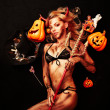 Beautiful devil with trident and Halloween accessories on black — Stockfoto #3921106