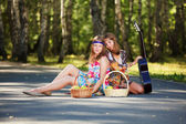 Hippie girls with guitar sitting on the road — Stock Photo