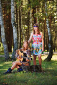 Hippie girls with guitar sitting on the stump — Stock Photo