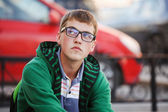 Young man sitting against a city traffic — Stock Photo