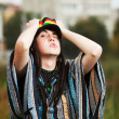 Young rastafarian man in a city park — Stock Photo