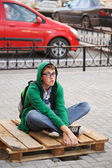 Young man sitting on a sidewalk — Stock Photo