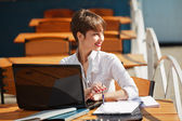 Young businesswoman with laptop at a sidewalk cafe — Stockfoto