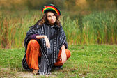 Young rastafarian woman in autumn park — Stock Photo