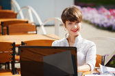 Young businesswoman with laptop at a sidewalk cafe — Stock fotografie