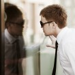 Young businessman looking through a window — Stock Photo
