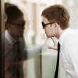 Young businessman looking through a window — Stock Photo #15459603