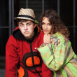 Young hippie couple against an iron fence — Stok fotoğraf