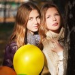 Young girls with a balloons in an autumn park — Stock Photo