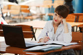 Young businesswoman with laptop at a sidewalk cafe — Stock Photo