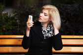 Young blond woman looking at mobile phone — Stock Photo