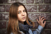Teenage girl against a brick wall — Stock Photo