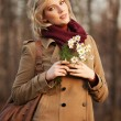 Young woman with a flowers in autumn forest — Stock Photo
