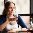 Beautiful young woman with cognac looking out the window — Stock Photo