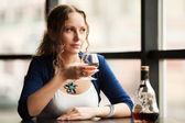 Giovane e bella donna con il cognac, guardando fuori dalla finestra — Foto Stock