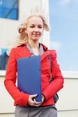 Young businesswoman with a folder against office windows. — Stock Photo