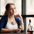 Beautiful young woman with cognac at restaurant — Stock Photo