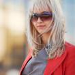 Young blond woman walking on a city street — Stock Photo #21295999