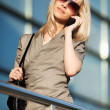 Blond woman calling on the phone against office windows — Stock Photo #21296077