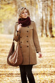 Young woman walking in autumn forest — Stock Photo
