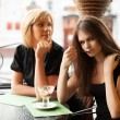 Two young women eating an ice cream at sidewalk cafe — Stock Photo #21698773