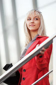 Young businesswoman on the steps against office windows — Stock Photo