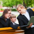 Young business with laptop in a city park — Stock Photo
