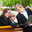 Stock Photo: Young business with laptop in a city park
