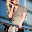 Blond woman calling on the phone against office windows — Stock Photo