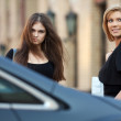 Two young women walking on the car parking — Stock Photo