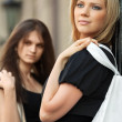 Two young women walking on a city street — Stock Photo