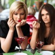 Two young women eating a dessert at sidewalk cafe — Stock Photo