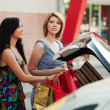 Two young women with shopping bags on the car parking — Stock Photo
