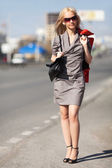 Happy young woman walking on the city street — Stock Photo