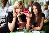 Two young women eating a dessert at sidewalk cafe — ストック写真