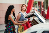 Dos mujeres jóvenes con bolsas de compras en el aparcamiento de coches — Foto de Stock