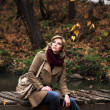 Young blond woman in autumn forest — Stock Photo