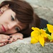 Young woman with a flowers lying on the tombstone — Stock Photo #24986397